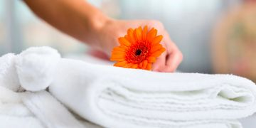Clean crisp white folded towels and linens  with an orange flower being placed on top