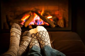 Warming up your feet sitting next to a fire in a fireplace