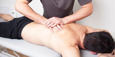 patient laying facedown while a chiropractor adjust the patients spine