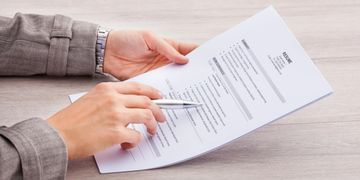 close up image of two hands holding a resume on a wooden surface