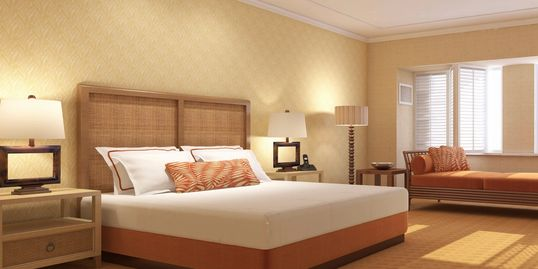 Brightly lit hotel room with wooden furniture in a natural finish, with bed neatly made for guest.