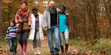 Happy family of mixed races walking through wooded area