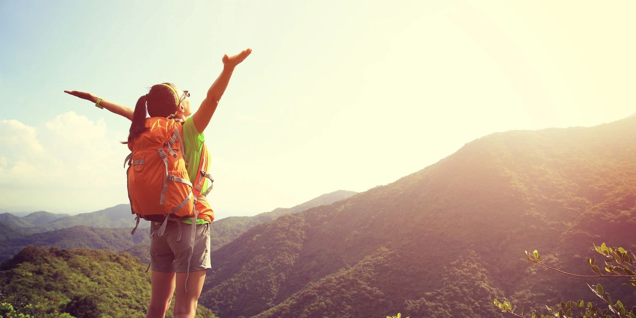 Excited Vibrant Woman hiking with orange backpack and hands to sky in mountains