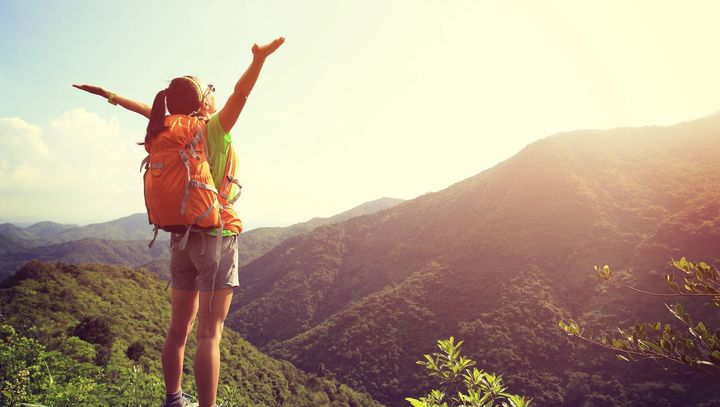 Woman hiker at top of mountain with outstretched arms celebrating