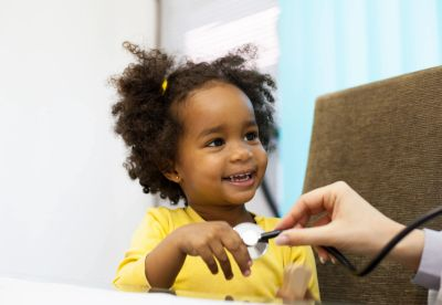 little girl smiling while being examined by pediatrician