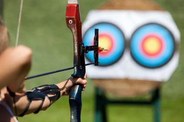 A bow and arrow pointed towards two bulls-eye targets.