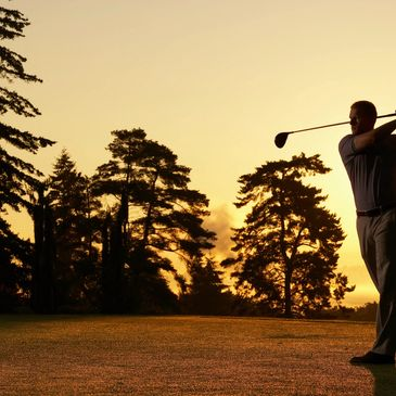 Golfer on golf course. The sun is setting behind trees and the lighting is exentuating the scene.