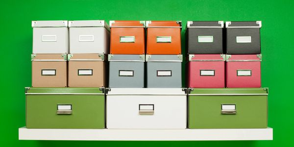 File boxes stacked up in front of green background.