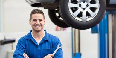 Mechanic with a wrench in front of a vehicle being repaired