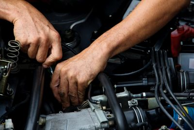 Mechanic hands performing auto repair in auto shop