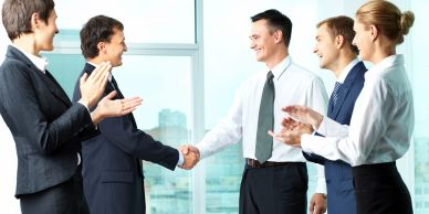 Group of professional people clapping with two people shaking hands.