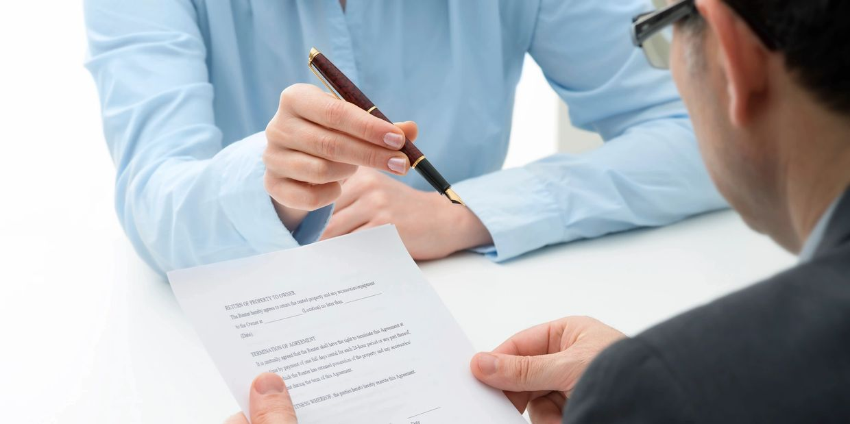 Woman handing pen to client to sign sale agreement without having a home inspection