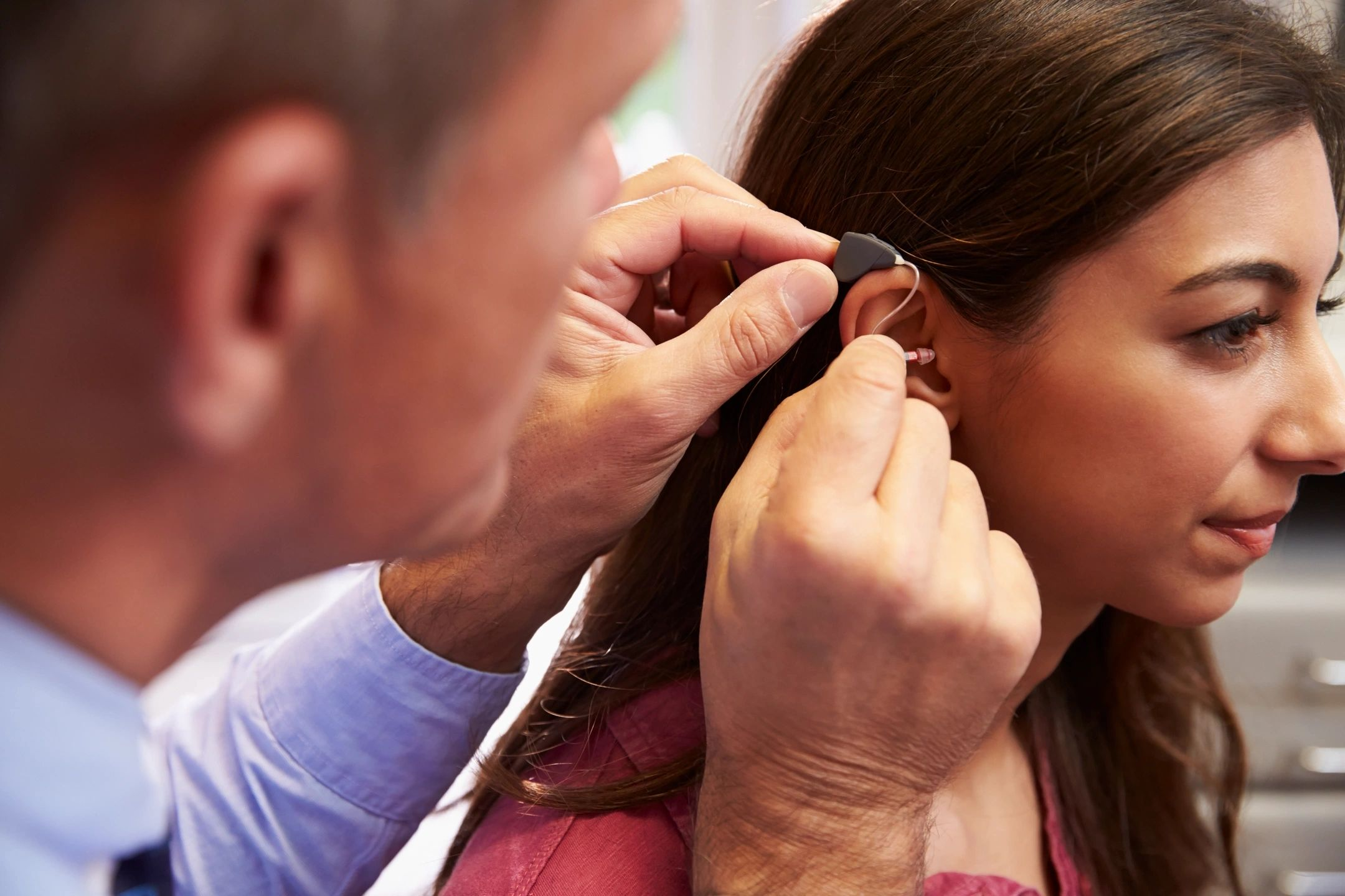 A picture of a young woman getting fitted for a hearing aid