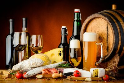 Display of food including bread and cheese, and glasses of wine and beer with bottles and a keg.