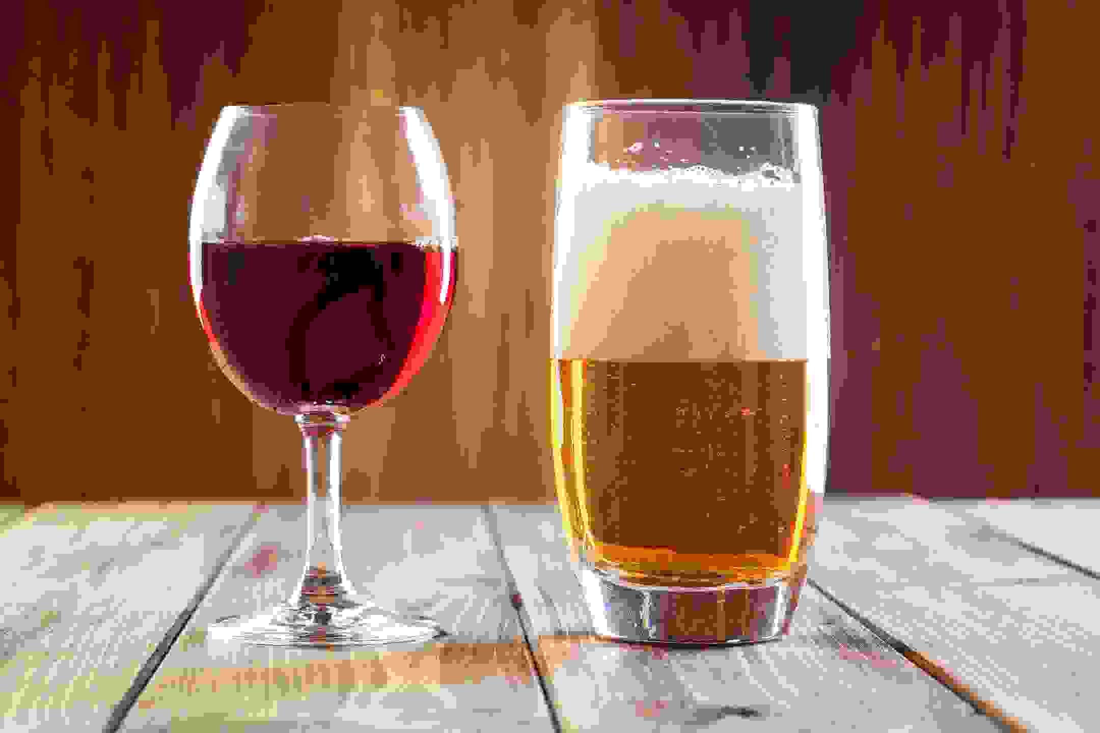 A glass of wine and a glass of beer with a frosty head, standing on a wooden table