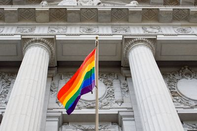 rainbow flag under and in front of large courthouse building with columns