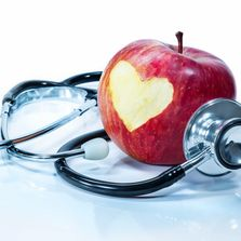 A red apple and a stethoscope.