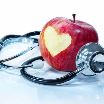 red apple with heart bitten out of it surrounded by a black tubed stethoscope on light blue desk