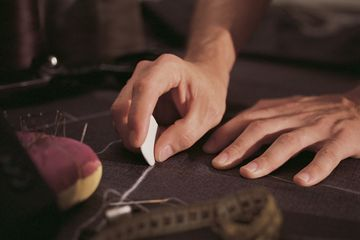 Tailor marking cloth with chalk. Pin cushion and tape measure visible. Dressmaking class.