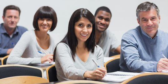 Several people are sitting in a class and smiling.
