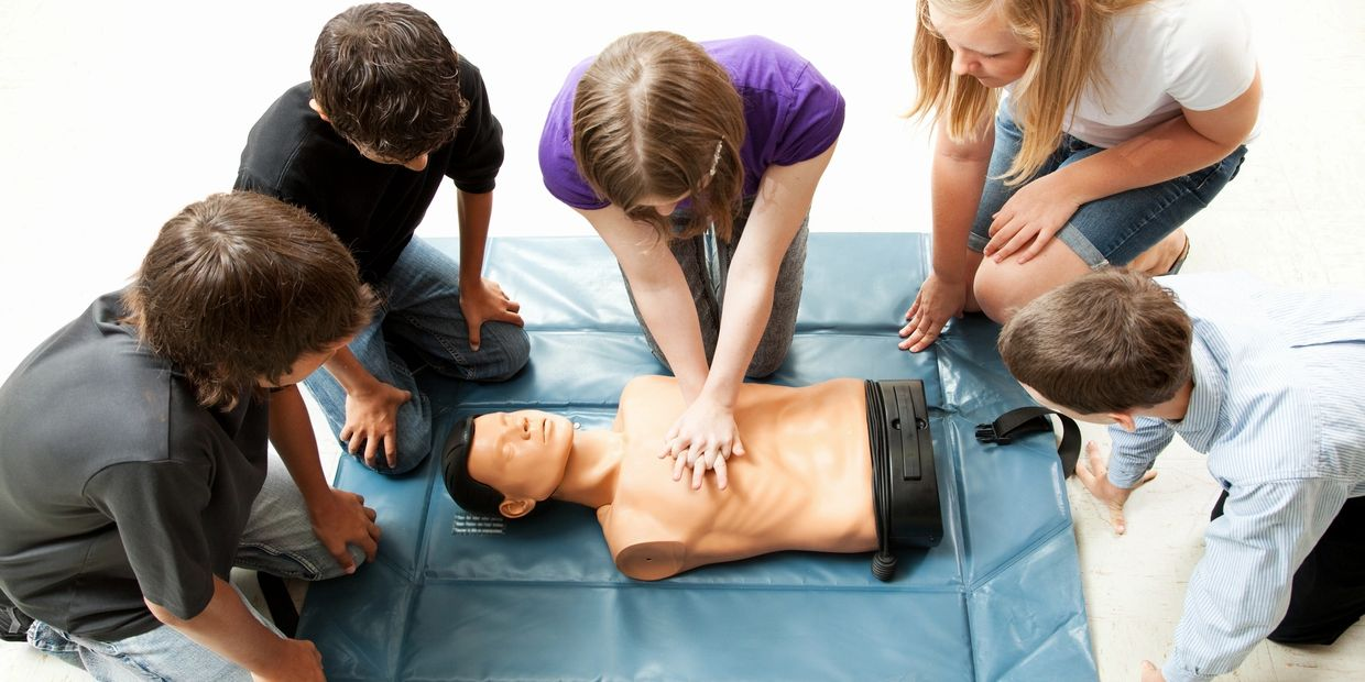 Children being taught first aid in school classroom