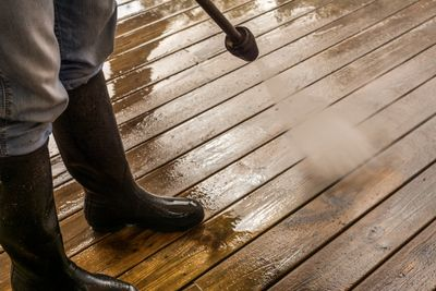 Someone pressure washing a wood deck