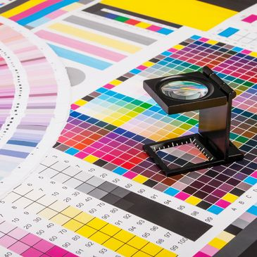 pantone colors and a magnifying device used in the printing industry