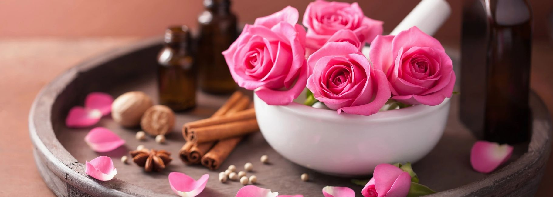 Four pink roses in a white bowl set on a larger brown plate which also holds 3 tincture bottles and a few rose petals are scattered about