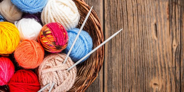 Basket of yarn balls and knitting needles