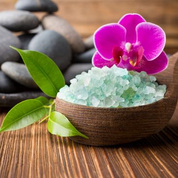Healing salts in a wooden spoon with orchid and river stones in the background