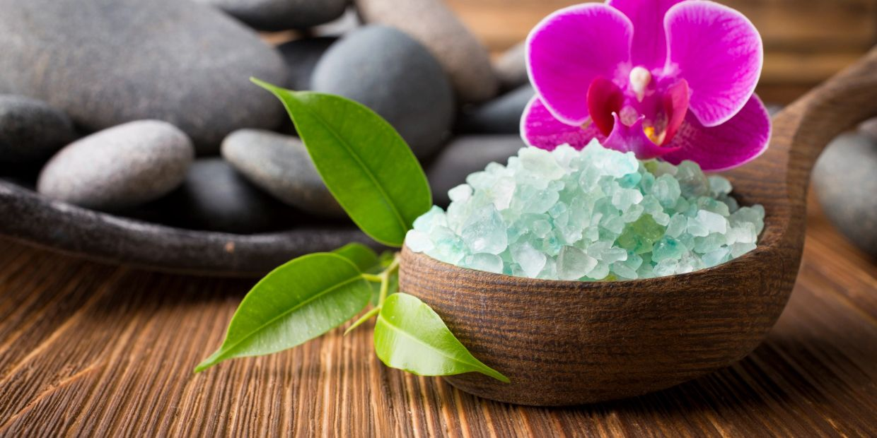 A relaxing image of healing stones, an orchid, and bath salts