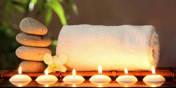 A calm, warm and serene spa setting with a white clean rolled towel and small white gently and warmly glowing tea light candles creating the ambience of a very calming and relaxing environment.