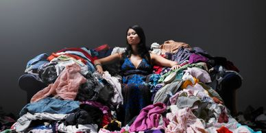 Woman surrounded by piles of clothing.