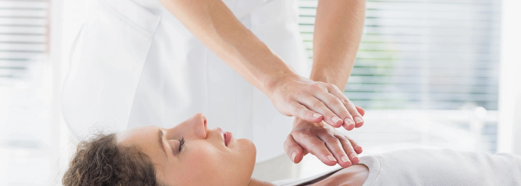 Reiki practitioner has placed their hands on the heart energy center of a client laying down.