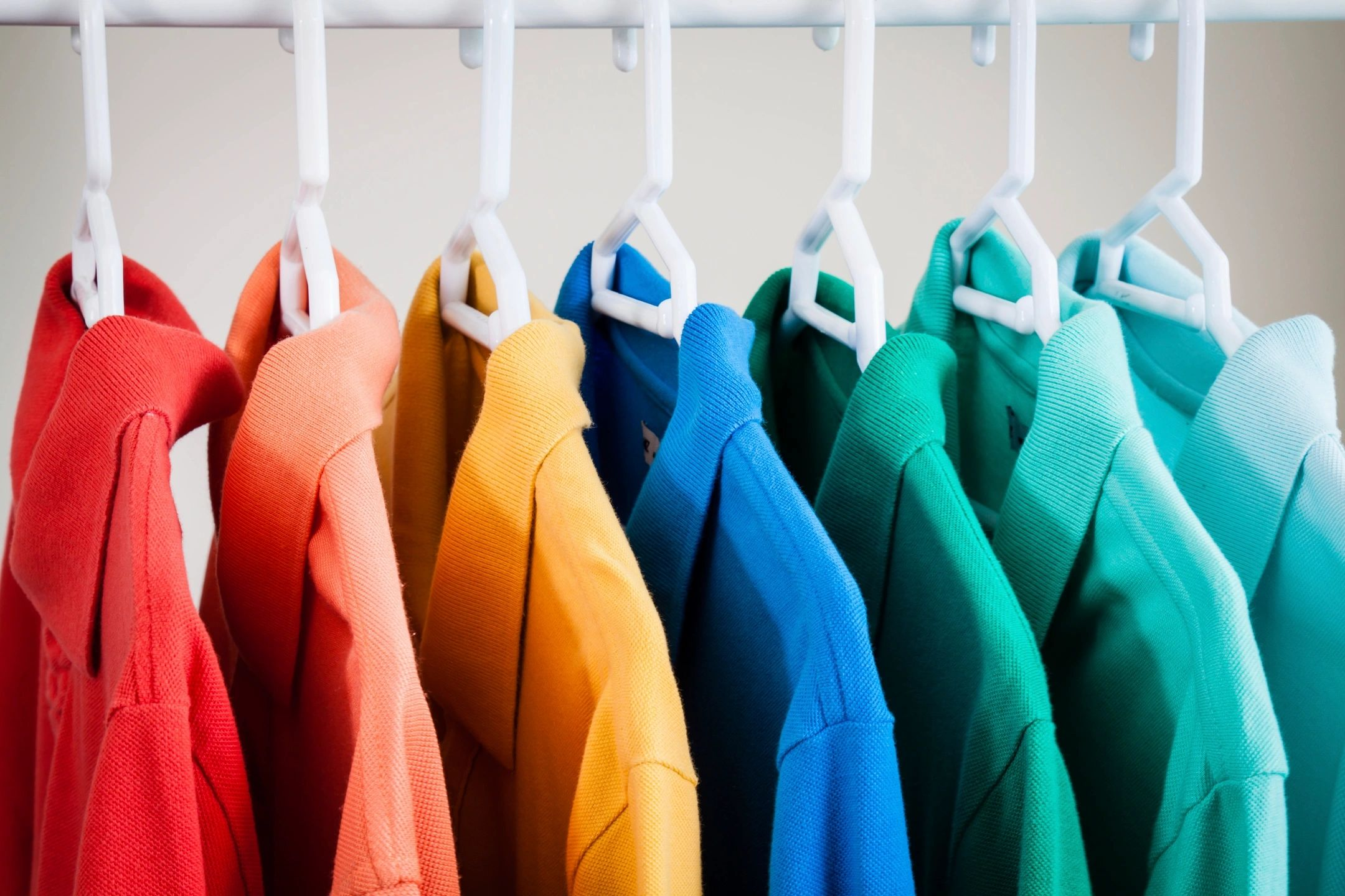 rainbow of shirts, hangers with multiple dry cleaned shirts, white hangers,