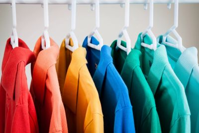 a row of colorful polo shirts on hangers