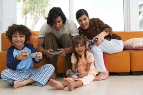 Two adults and two children playing computer game