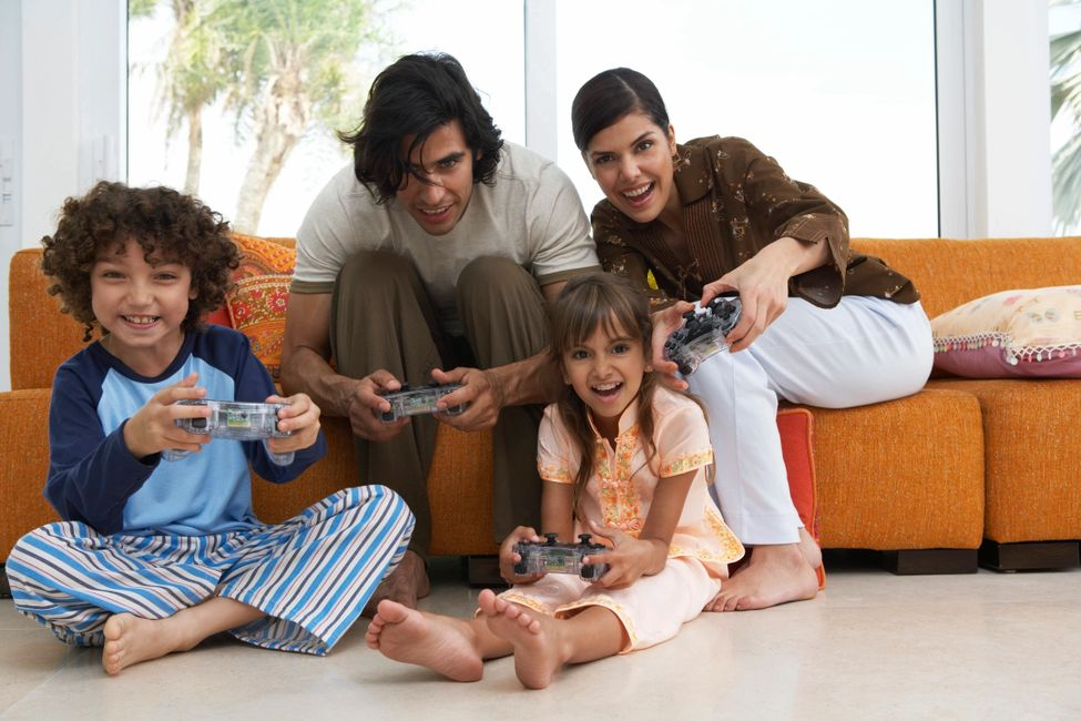 Picture of a man and a woman sitting on sofa playing video game with a boy and a girl