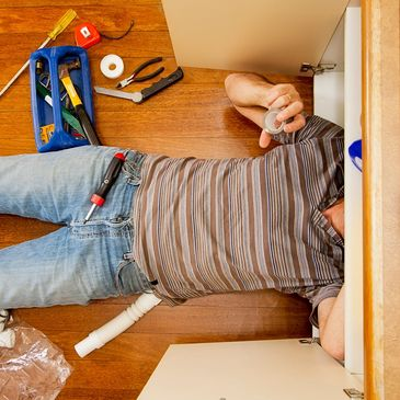 Plumber lying on back working
