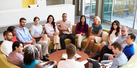 Group of adults sitting in a circle with attention directed to a speaker.