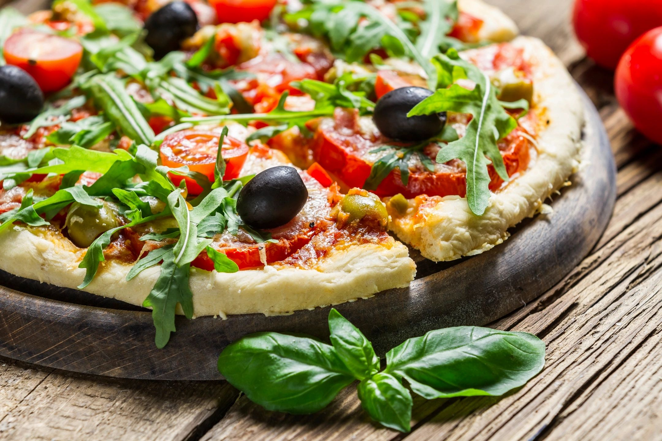 Pizza on cutting board with fresh olives and arugula
