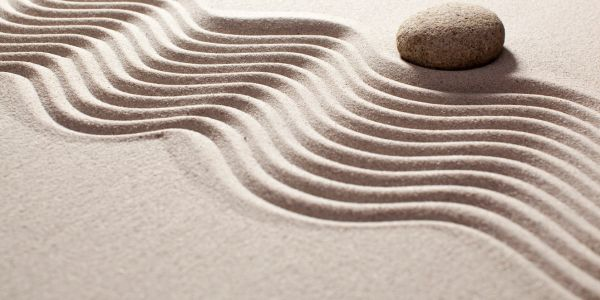 A stone sits beside perfectly drawn ridges in sand.
