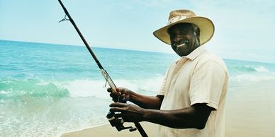 black guy who is happy wearing a sun hat fishing on the shore www.glassbottomtours.com