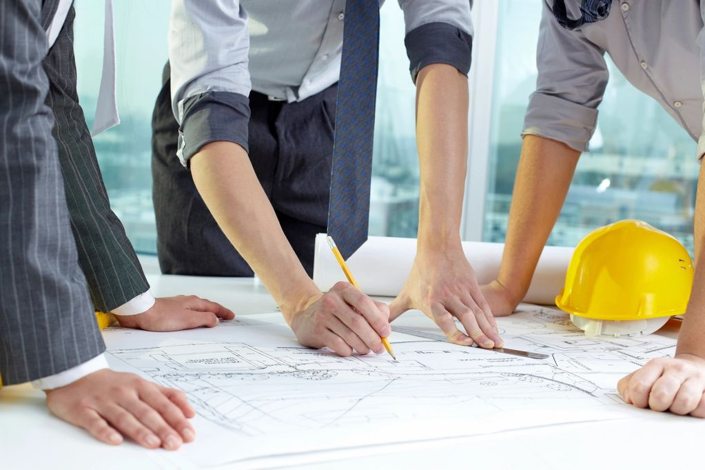 Drainage Design.  A team of civil engineers stand over a set of drainage plans.  One holds a pencil.