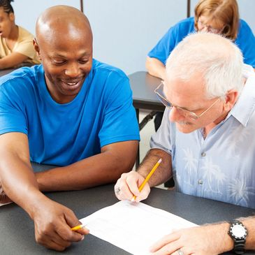 For screen readers - an image of an African American man helping an older Caucasian man study