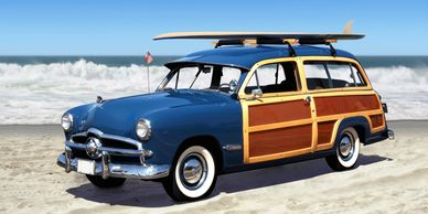 Classic Woody car with a surfboard on the roof sits on the beach