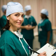 A woman in surgical scrubs is smiling and holding a clipboard.
