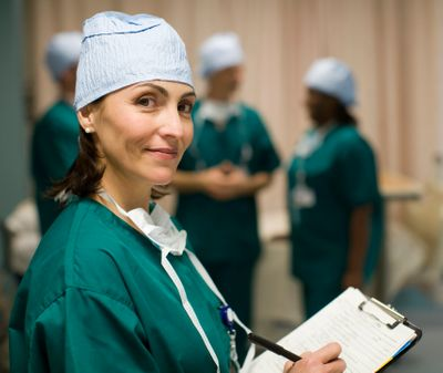 A female medical professional is smiling; she's wearing surgical scrubs & holding a clipboard & pen.