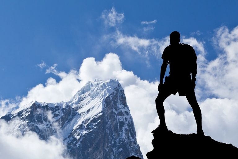image of mountain climber gazing up at the snowy summit ahead