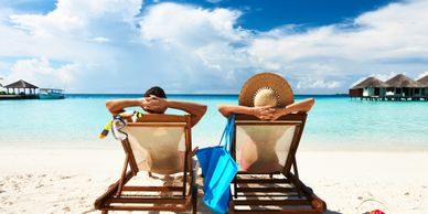 Couple on vacation relaxing on a beach in lounge chairs.